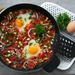 Eenpansgerecht van eieren in lichtpittige groenten
